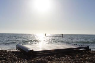 solar thermal panel on the beach with paddle boarders int he distance
