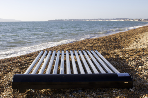 Solar thermal renewable energy panel sitting on a pebble beach by the waves